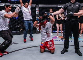 Kevin Belingon of Team Lakay kneeling down while having his hand raised by the referee in victory. (Photo: ONE Championship)